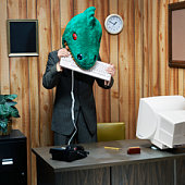 Dinosaur in office eating computer keyboard