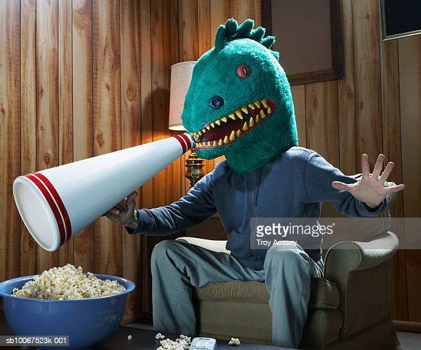 Dinosaur watching TV. and cheering with megaphone