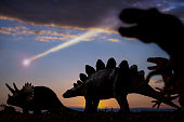 Dinosaurs and a meteor falling from the sky in back background.