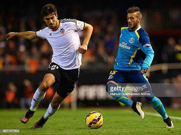 Diogo of Sevilla runs with the ball behind Andre Gomes of Valencia during the La Liga match between Valencia CF and Sevilla FC at Estadi de Mestalla...