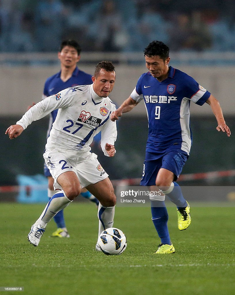 Diogo (L) of Vegalta Sendaion challenges Lu Baofei of Jiangsu Sainty during the AFC Champions League match between Jiangsu Sainty and Vegalta Sendai at Nanjing Olympic Sports Center Stadium on March 12, 2013 in Nanjing, China.