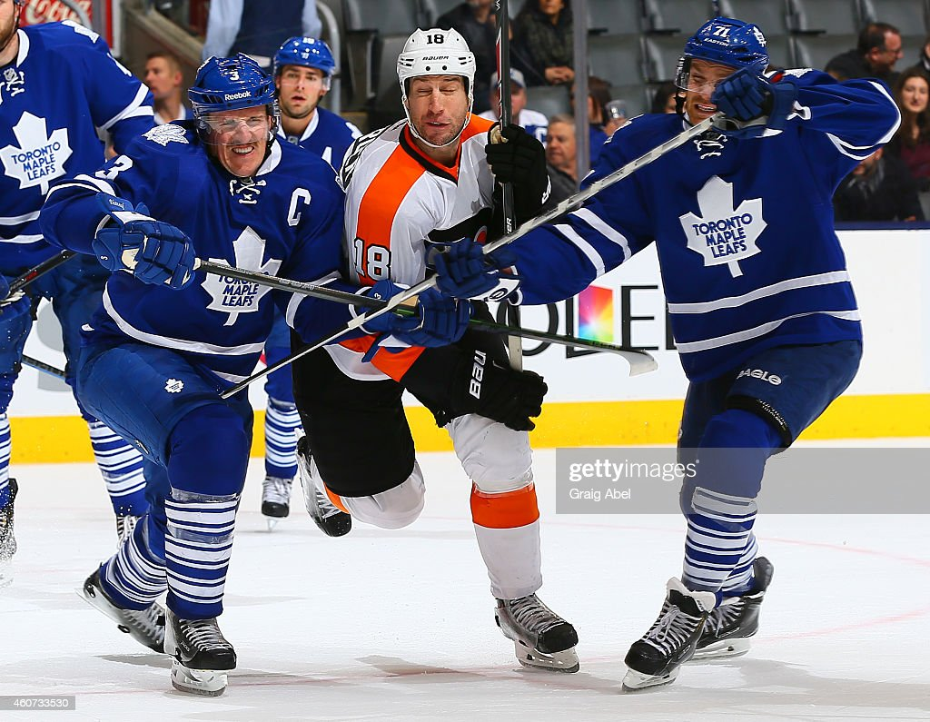 Dion Phaneuf and David Clarkson of the Toronto Maple Leafs hold up RJ Umberger of the Philadelphia Flyers during NHL game action December 20 2014 at...