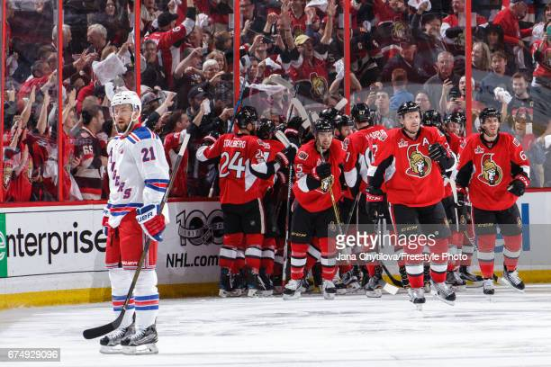 Dion Phaneuf and Mike Hoffman of the Ottawa Senators celebrate their overtime win as Derek Stepan of the New York Rangers sates off the ice in Game...