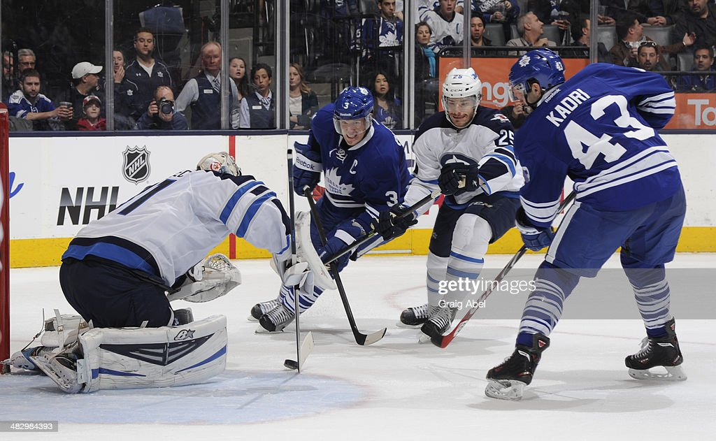 <a gi-track='captionPersonalityLinkClicked' href=/galleries/search?phrase=Dion+Phaneuf&family=editorial&specificpeople=545455 ng-click='$event.stopPropagation()'>Dion Phaneuf</a> #3 and <a gi-track='captionPersonalityLinkClicked' href=/galleries/search?phrase=Nazem+Kadri&family=editorial&specificpeople=4043234 ng-click='$event.stopPropagation()'>Nazem Kadri</a> #43 of the Toronto Maple Leafs battle for the puck with <a gi-track='captionPersonalityLinkClicked' href=/galleries/search?phrase=Zach+Redmond&family=editorial&specificpeople=8234699 ng-click='$event.stopPropagation()'>Zach Redmond</a> #25 of the Winnipeg Jets as goalie Ondrej Pavelec #31 reaches for the puck during NHL game action April 5, 2014 at the Air Canada Centre in Toronto, Ontario, Canada.