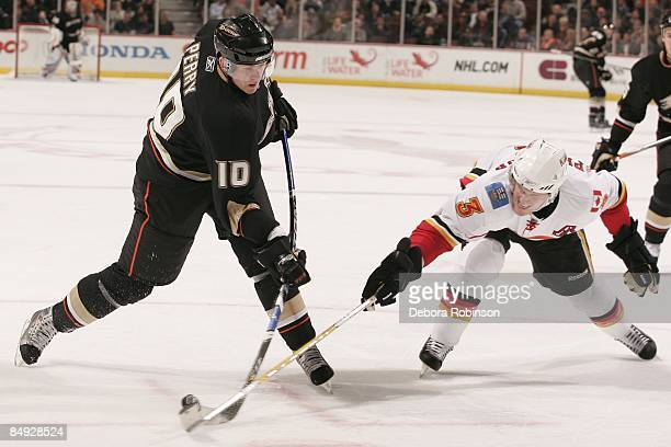 Dion Phaneuf of the Calgary Flames reaches for the puck against Corey Perry of the Anaheim Ducks during the game on February 11 2009 at Honda Center...