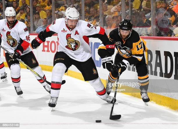 Dion Phaneuf of the Ottawa Senators and Bryan Rust of the Pittsburgh Penguins battle for the loose puck in Game Five of the Eastern Conference Final...