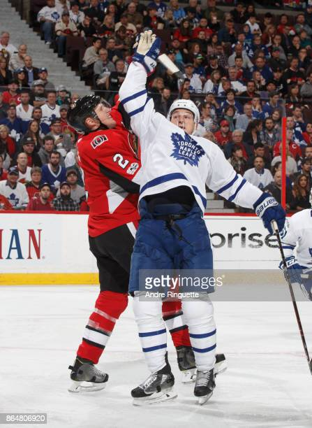 Dion Phaneuf of the Ottawa Senators and Zach Hyman of the Toronto Maple Leafs reach up for a falling puck during an NHL game at Canadian Tire Centre...