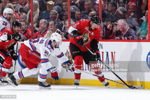 Dion Phaneuf of the Ottawa Senators battles for the loose puck against Mika Zibanejad of the New York Rangers in Game Two of the Eastern Conference...