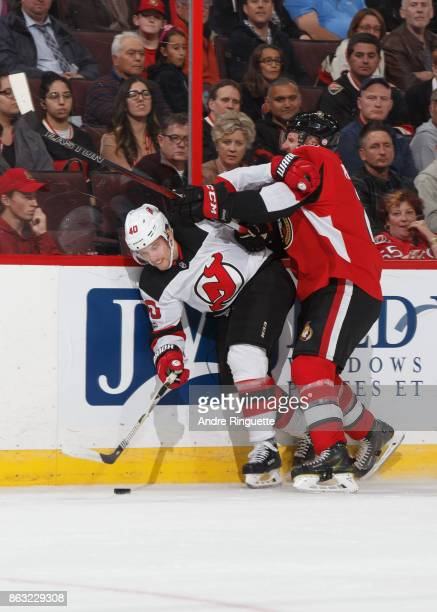 Dion Phaneuf of the Ottawa Senators body checks Blake Coleman of the New Jersey Devils against the boards at Canadian Tire Centre on October 19 2017...