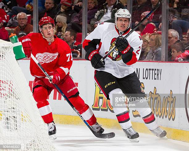 Dion Phaneuf of the Ottawa Senators skates behind the net next to Dylan Larkin of the Detroit Red Wings during an NHL game at Joe Louis Arena on...