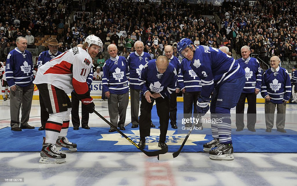 Dion Phaneuf #3 of the Toronto Maple Leafs and Daniel Alfredsson #11 of the Ottawa Senators take part in an ceremonial face-off with Johnny Bower honouring the 1963 Stanley Cup winning Toronto Maple Leafs prior to NHL game action February 16, 2013 at the Air Canada Centre in Toronto, Ontario, Canada.