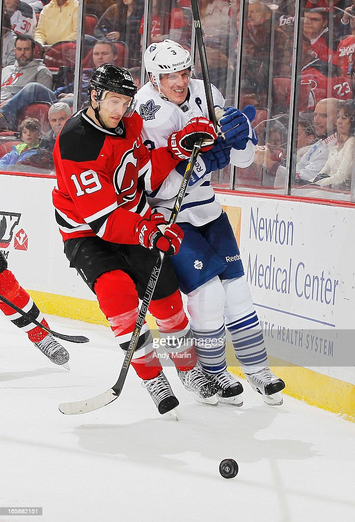 Dion Phaneuf #3 of the Toronto Maple Leafs and Travis Zajac #19 of the New Jersey Devils battle for a loose puck during the game at the Prudential Center on April 6, 2013 in Newark, New Jersey.