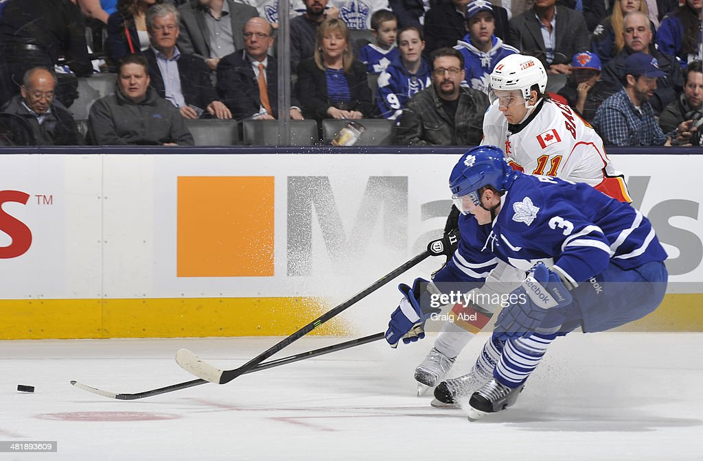 Dion Phaneuf #3 of the Toronto Maple Leafs battles for the puck with Mikael Backlund #11 of the Calgary Flames during NHL game action April 1, 2014 at the Air Canada Centre in Toronto, Ontario, Canada.