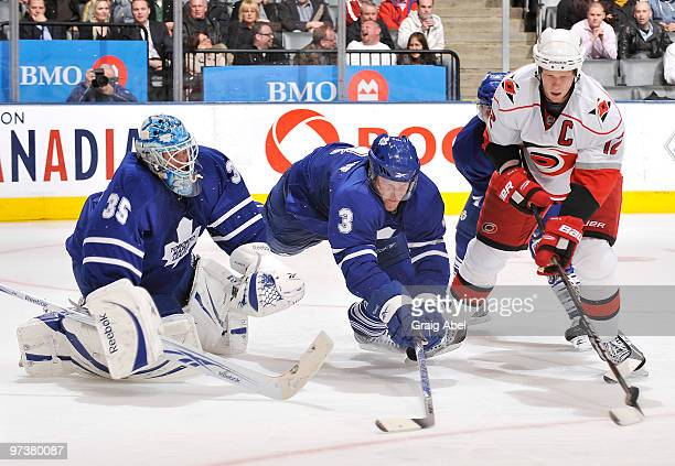 Dion Phaneuf of the Toronto Maple Leafs battles for the puck with Eric Staal of the Carolina Hurricanes in front of goalie JeanSebastien Giguere...