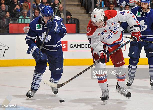 Dion Phaneuf of the Toronto Maple Leafs battles for the puck with Tom Wilson of the Washington Capitals during NHL game action November 29 2014 at...
