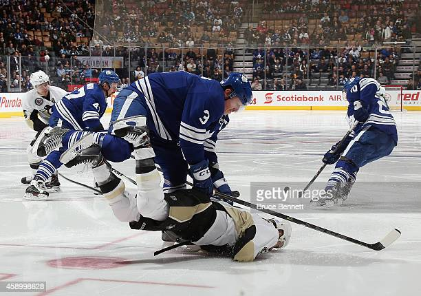 Dion Phaneuf of the Toronto Maple Leafs checks Pascal Dupuis of the Pittsburgh Penguins during the second period at the Air Canada Centre on November...