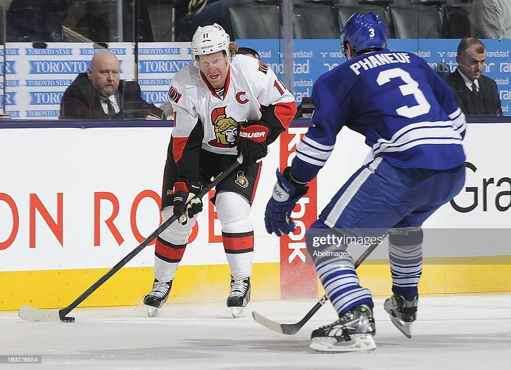 Dion Phaneuf #3 of the Toronto Maple Leafs defends as Daniel Alfredsson #11 of the Ottawa Senators looks to pass the puck during NHL game action March 6, 2013 at the Air Canada Centre in Toronto, Ontario, Canada.