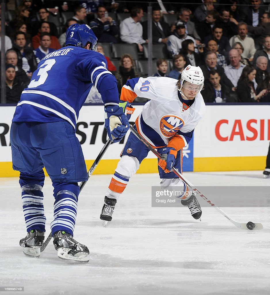 Dion Phaneuf #3 of the Toronto Maple Leafs defends as Michael Grabner #40 of the New York Islanders shoots the puck during NHL game action January 24, 2013 at the Air Canada Centre in Toronto, Ontario, Canada.