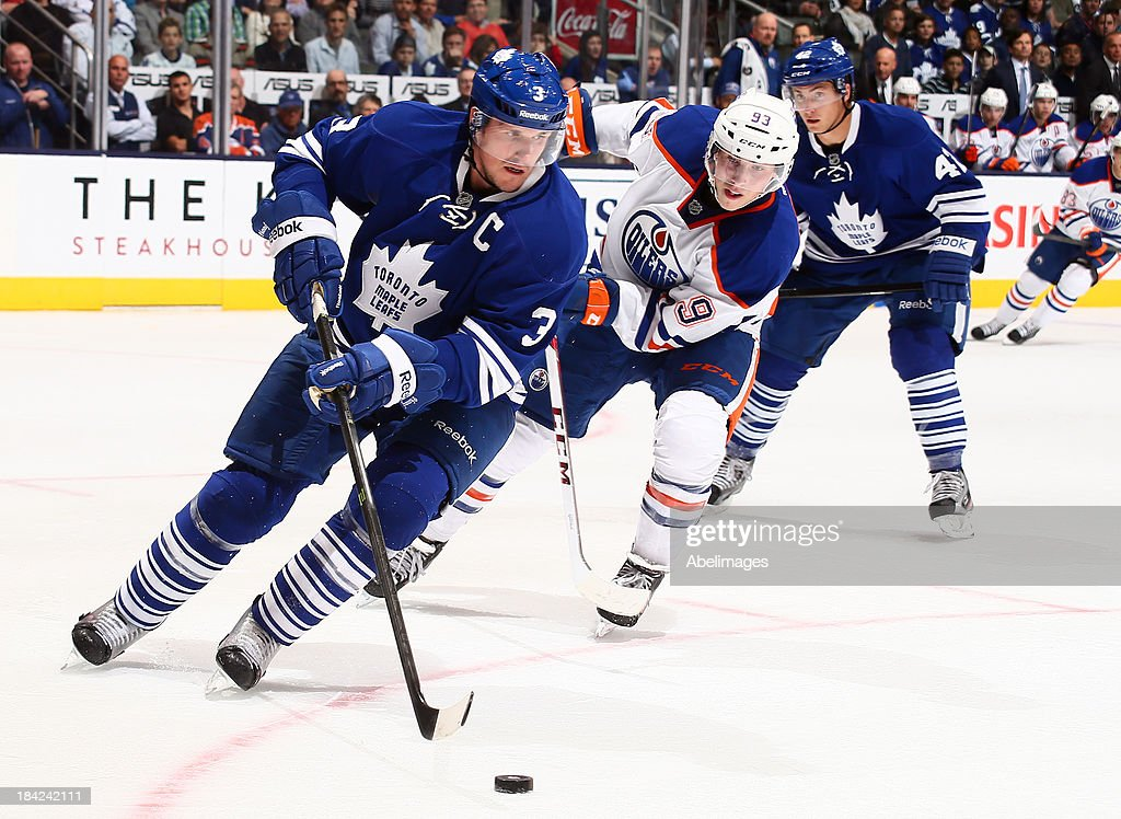 <a gi-track='captionPersonalityLinkClicked' href=/galleries/search?phrase=Dion+Phaneuf&family=editorial&specificpeople=545455 ng-click='$event.stopPropagation()'>Dion Phaneuf</a> #3 of the Toronto Maple Leafs gets away from <a gi-track='captionPersonalityLinkClicked' href=/galleries/search?phrase=Ryan+Nugent-Hopkins&family=editorial&specificpeople=7144190 ng-click='$event.stopPropagation()'>Ryan Nugent-Hopkins</a> #93 of the Edmonton Oilers during NHL action at the Air Canada Centre October 12, 2013 in Toronto, Ontario, Canada.