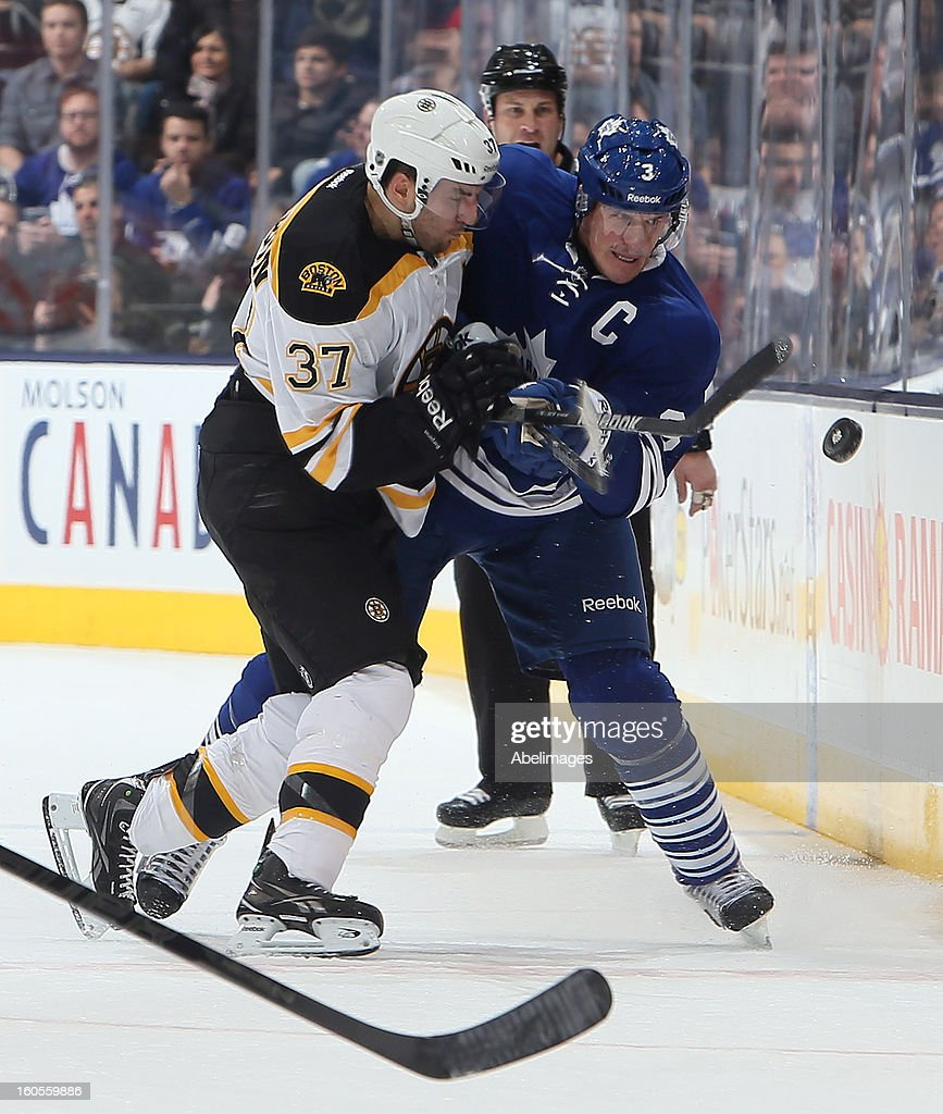 Dion Phaneuf #3 of the Toronto Maple Leafs gets the puck past Patrice Bergeron #37 of the Boston Bruins during NHL action at the Air Canada Centre February 2, 2013 in Toronto, Ontario, Canada.