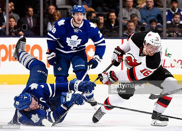 Dion Phaneuf of the Toronto Maple Leafs is upended by Jacob Josefson of the New Jersey Devils during game action on December 8 2015 at Air Canada...