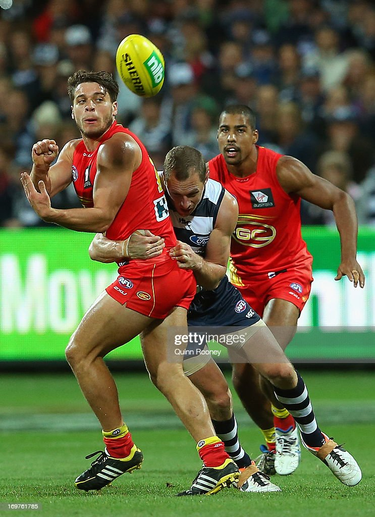 Dion Prestia of the Suns handballs whilst being tackled by James Kelly of the Cats during the round ten AFL match between the Geelong Cats and the Gold Coast Suns at Simonds Stadium on June 1, 2013 in Geelong, Australia.