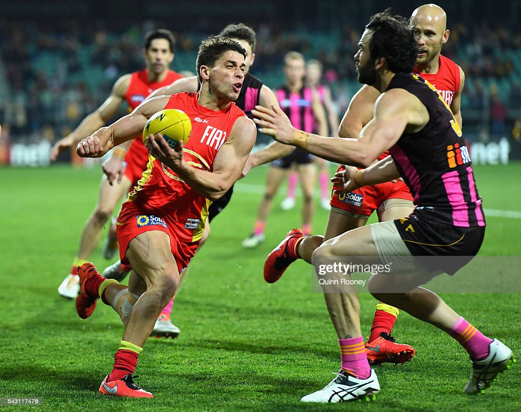 Dion Prestia of the Suns handballs whilst being tackled by <a gi-track='captionPersonalityLinkClicked' href=/galleries/search?phrase=Jordan+Lewis&family=editorial&specificpeople=236095 ng-click='$event.stopPropagation()'>Jordan Lewis</a> of the Hawks during the round 14 AFL match between the Hawthorn Hawks and the Gold Coast Suns at Aurora Stadium on June 26, 2016 in Launceston, Australia.