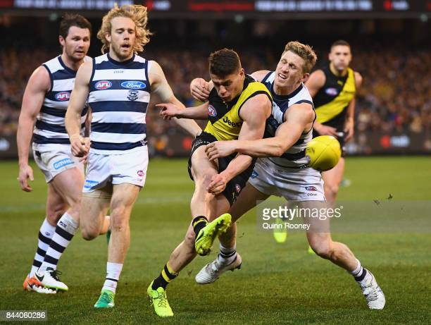 Dion Prestia of the Tigers kicks whilst being tackled by Scott Selwood of the Cats during the AFL Second Qualifying Final Match between the Geelong...