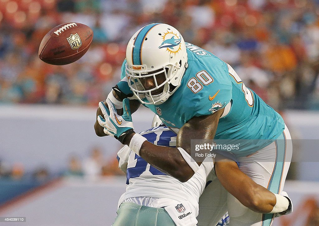 Dion Sims #80 of the Miami Dolphins fumbles in the second quarter after Ahmad Dixon #36 of the Dallas Cowboys made contact during a preseason game at Sun Life Stadium on August 23, 2014 in Miami Gardens, Florida.