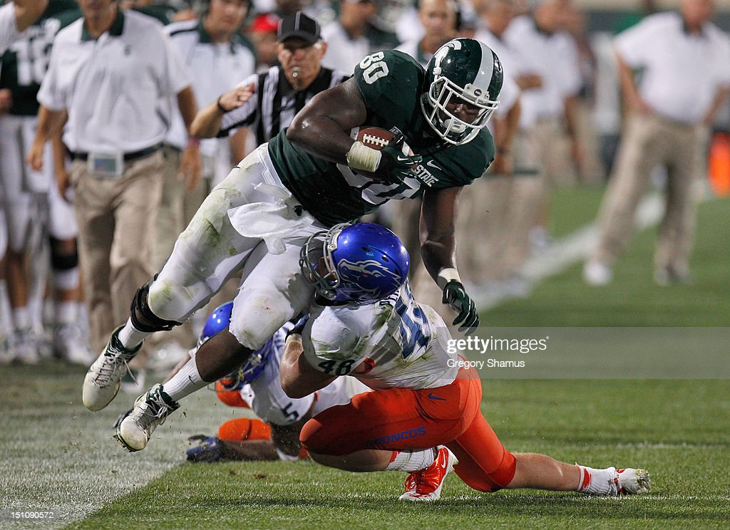 Dion Sims #80 of the Michigan State Spartans is tackled near the sideline after a fourth quarter catch by J.C. Percy #48 of the Boise State Broncos at Spartan Stadium on August, 2010 in East Lansing, Michigan. Michigan State won the game 17-13.