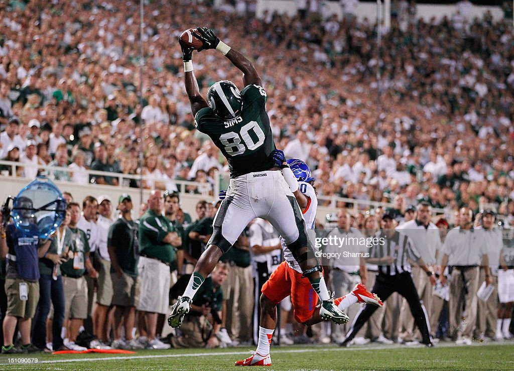 Dion Sims #80 of the Michigan State Spartans makes a fourth quarter catch behind the defense of Jeremy Ioane #10 of the Boise State Broncos at Spartan Stadium on August, 2010 in East Lansing, Michigan. Michigan State won the game 17-13.