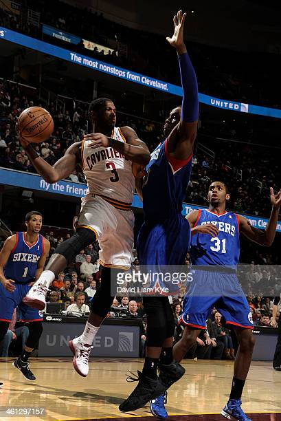 Dion Waiters of the Cleveland Cavaliers passes to a teammate from under the basket against Lavoy Allen of the Philadelphia 76ers at The Quicken Loans...
