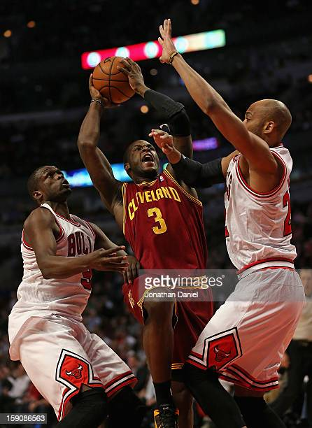 Dion Waiters of the Cleveland Cavaliers puts up a shot between Loul Deng and Taj Gibson of the Chicago Bulls at the United Center on January 7 2013...
