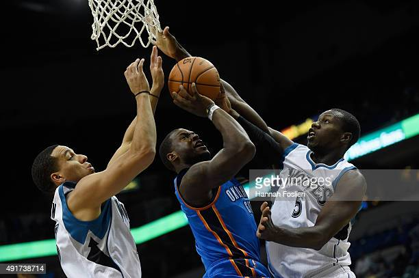 Dion Waiters of the Oklahoma City Thunder shoots a basket against Kevin Martin and Gorgui Dieng of the Minnesota Timberwolves during the first...