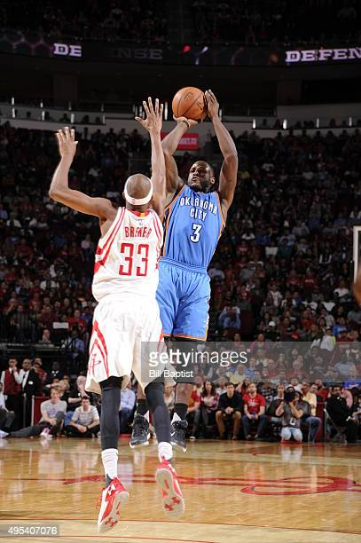 Dion Waiters of the Oklahoma City Thunder shoots against Corey Brewer of the Houston Rockets on November 2 2015 at the Toyota Center in Houston Texas...