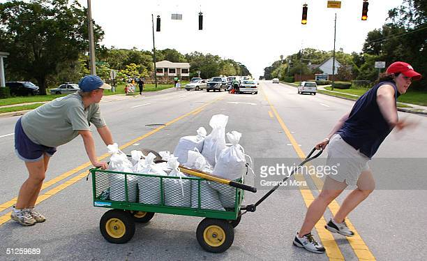 Dione Souza and Terry Hirtz pull a wagon loaded with sandbags in preparation for Hurricane Frances September 3 2004 in Orlando Florida Hurricane...