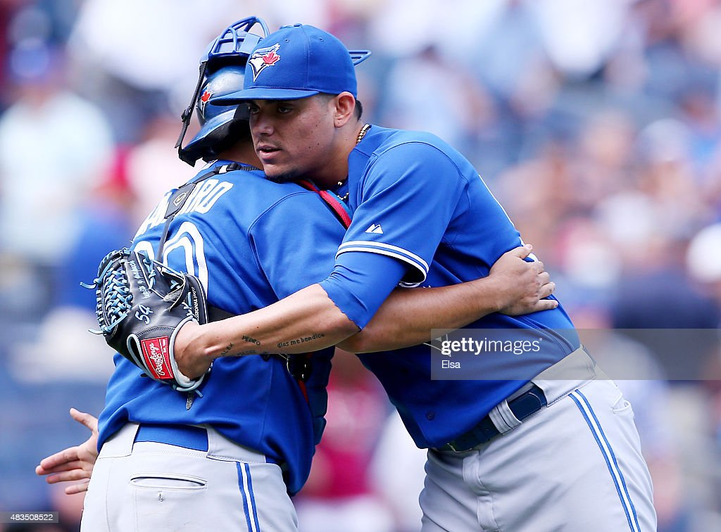 Dioner Navarro #30 and Roberto Osuna #54 of the Toronto Blue Jays celebrate the 2-1 win over the New York Yankees on August 9, 2015 at Yankee Stadium in the Bronx borough of New York City.