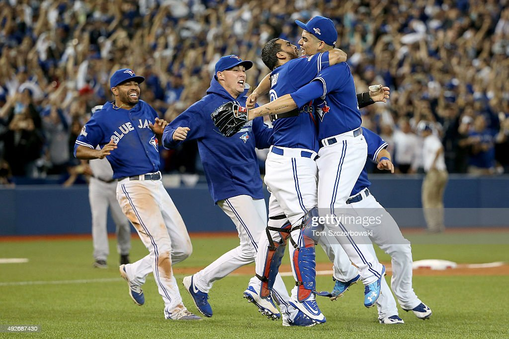 Dioner Navarro #30 and Roberto Osuna #54 of the Toronto Blue Jays celebrate the 6-3 win against the Texas Rangers as Ben Revere #7 jumps on top of the pile in game five of the American League Division Series at Rogers Centre on October 14, 2015 in Toronto, Canada.