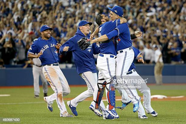 Dioner Navarro and Roberto Osuna of the Toronto Blue Jays celebrate the 63 win against the Texas Rangers as Ben Revere jumps on top of the pile in...