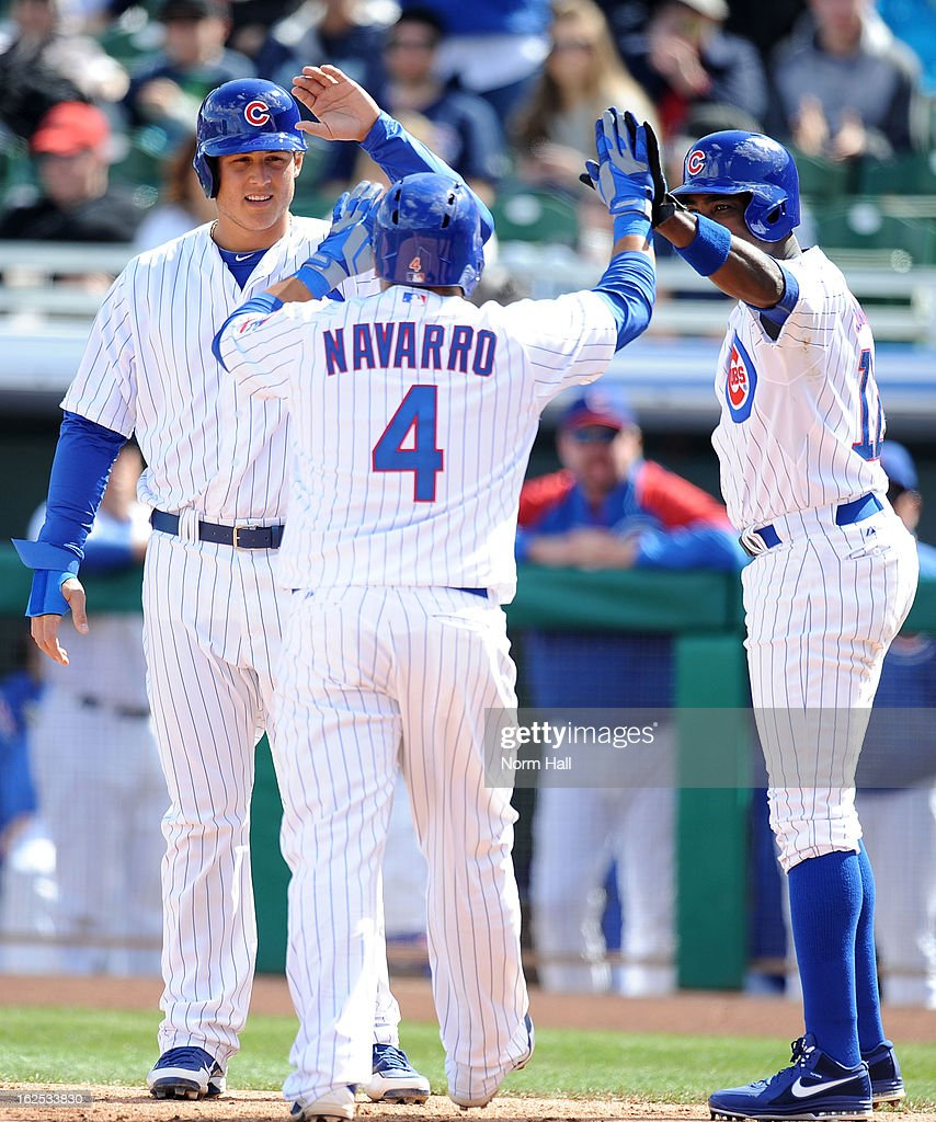 <a gi-track='captionPersonalityLinkClicked' href=/galleries/search?phrase=Dioner+Navarro&family=editorial&specificpeople=593062 ng-click='$event.stopPropagation()'>Dioner Navarro</a> #4 of the Chicago Cubs and teammates <a gi-track='captionPersonalityLinkClicked' href=/galleries/search?phrase=Anthony+Rizzo&family=editorial&specificpeople=7551494 ng-click='$event.stopPropagation()'>Anthony Rizzo</a> #44 and <a gi-track='captionPersonalityLinkClicked' href=/galleries/search?phrase=Alfonso+Soriano&family=editorial&specificpeople=202251 ng-click='$event.stopPropagation()'>Alfonso Soriano</a> #12 celebrate a home run against the San Francisco Giants at HoHoKam Park on February 24, 2013 in Mesa, Arizona.