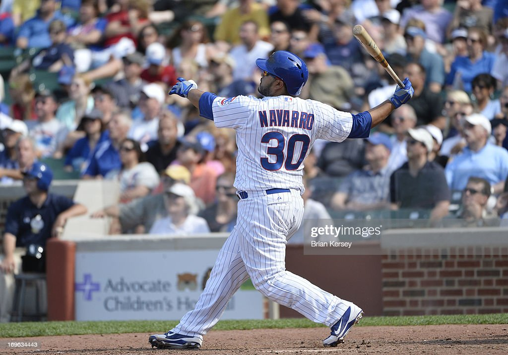 Dioner Navarro #30 of the Chicago Cubs follows through on a three-run home run scoring teammates Alfonso Soriano #12 and Anthony Rizzo #44 during the seventh inning against the Chicago White Sox at Wrigley Field on May 29, 2013 in Chicago, Illinois.