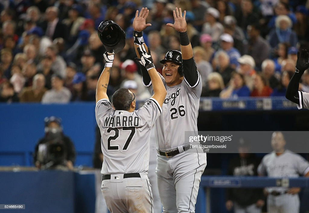 Dioner Navarro #27 of the Chicago White Sox is congratulated by Avisail Garcia #26 after hitting a two-run home run in the seventh inning during MLB game action against the Toronto Blue Jays on April 26, 2016 at Rogers Centre in Toronto, Ontario, Canada.