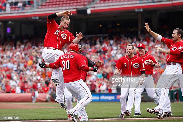 Dioner Navarro of the Cincinnati Reds gets mobbed by teammates after hitting a triple to drive in the gamewinning run in the ninth inning against the...