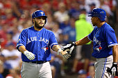 Dioner Navarro of the Toronto Blue Jays celebrates with Ben Revere after scoring a run off Ryan Goins against Martin Perez of the Texas Rangers...