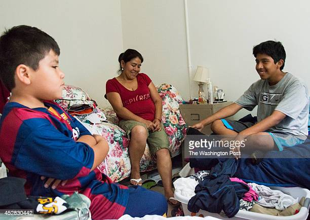 Dionicia Gomez center poses for a portrait with her two sons Danery Lobo and Henry Torres in their bedroom of the apartment where they share it with...