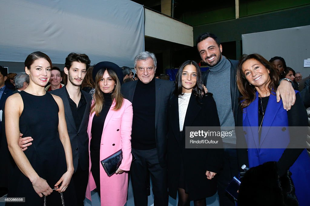 Dior Sidney Toledano (C), his wife Katia Toledano (R), their son Alan Toledano (2nd R) with his companion Joy Taieb (3rd R), their daughter Julia Toledano (3rd L), Actors Pierre Niney (2nd L) and his Companion Natasha Andrews (L) attend the Dior Homme Menswear Fall/Winter 2015-2016 Show as part of Paris Fashion Week on January 24, 2015 in Paris, France.