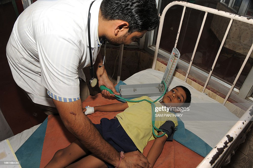 Dipak Hiralal, 6, a pupil at an Ahmedabad Municipal Corporation-run school, receives treatment for food poisoning at the Civil Hospital in Ahmedabad on April 9, 2013. A girl has died and eight other schoolchildren hospitalised after drinking contaminated water in a school in Asarava area of the city, a local report said. AFP PHOTO / Sam PANTHAKY