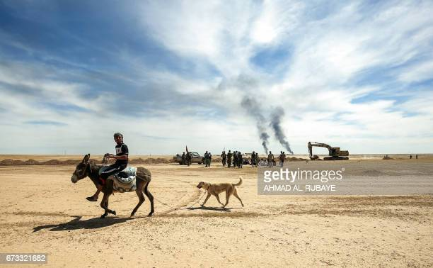 TOPSHOT A diplaced Iraqi man rides a donkey followed by his dog as progovernment Hashed alShaabi paramilitary forces advance towards the UNESCOlisted...