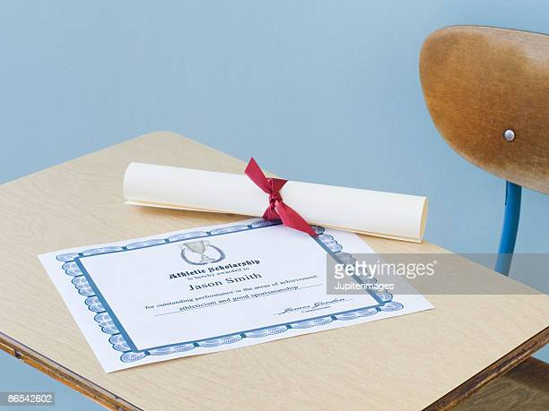 Diploma and certificate of achievement on school desk