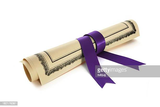 A diploma rolled up with a purple ribbon wrapped around it
